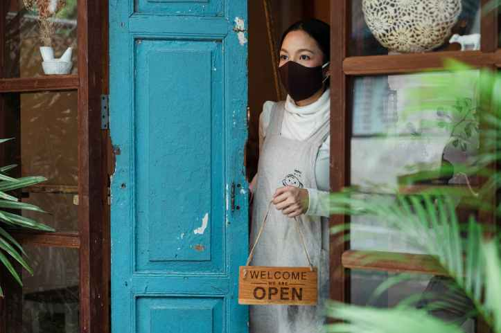 serious ethnic woman at rural shop doorway